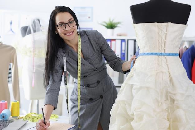 Couturière femme écrivant les tailles de robe de mariée.