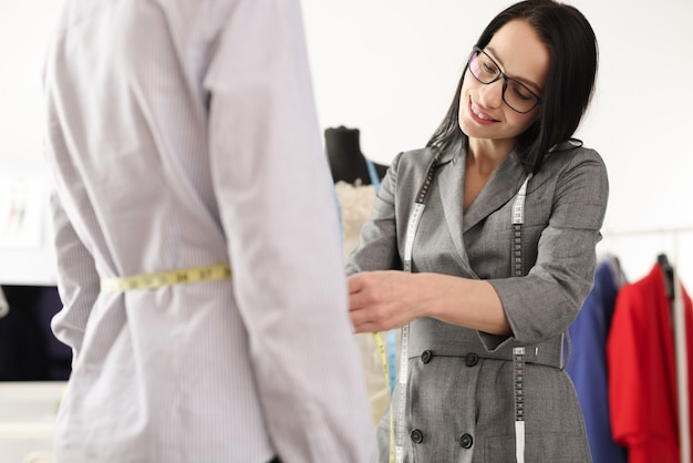 Couturière femme mesurant la taille du client avec réparation de ruban centimétrique et réparation de vêtements