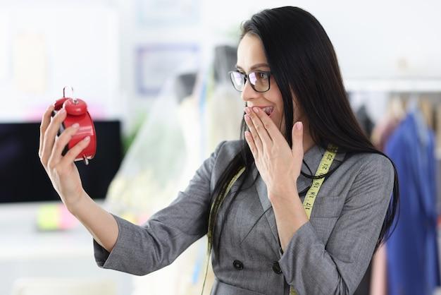 Couturière femme regarde réveil rouge avec surprise. délais du projet pendant la conception