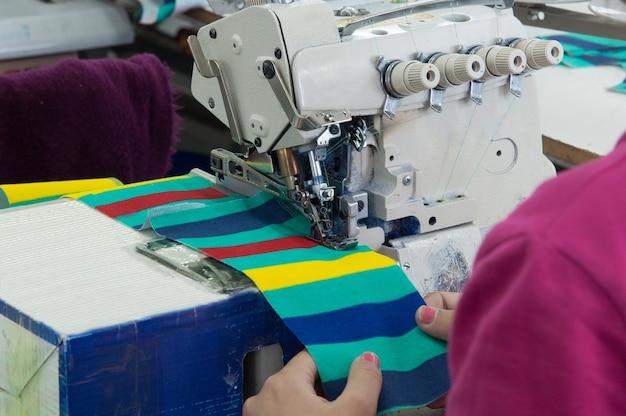 La couturière en gros plan sur la machine coud des vêtements dans une usine de confection