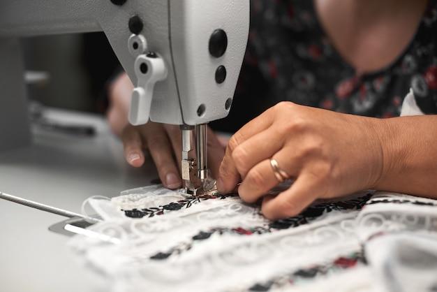 Couturière mains couture sur machine moderne