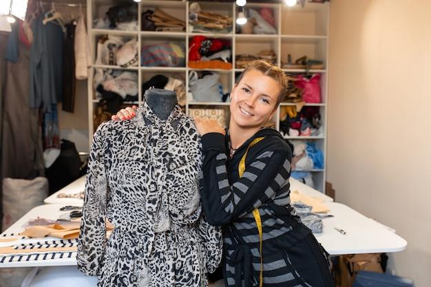 Couturière avec mannequin en tant que créatrice de mode professionnelle. couturière femme ajustant les vêtements sur couture mannequin et souriant