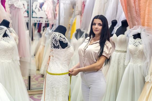 Couturière mesurant la taille en robe de mariée dans le salon