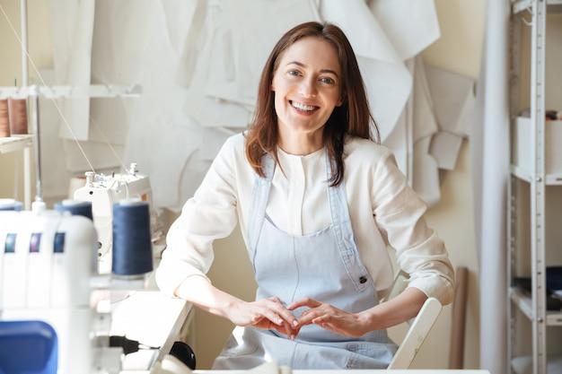 Couturière à la recherche et souriant