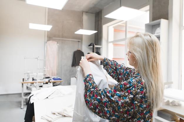 La couturière se tient dans le studio près du mannequin et ajuste les vêtements.