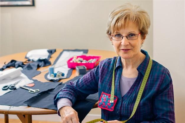 Couturière senior posant regardant la caméra avec table avec du matériel de couture en arrière-plan