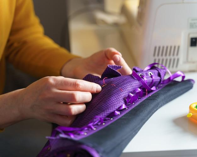 Couturière ou tailleur à l'aide d'un crochet à coudre tout en faisant un corset