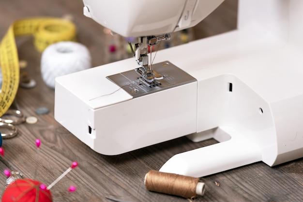 Couturière ou tailleur de fond avec des outils de couture, des fils colorés, une machine à coudre et des accessoires.