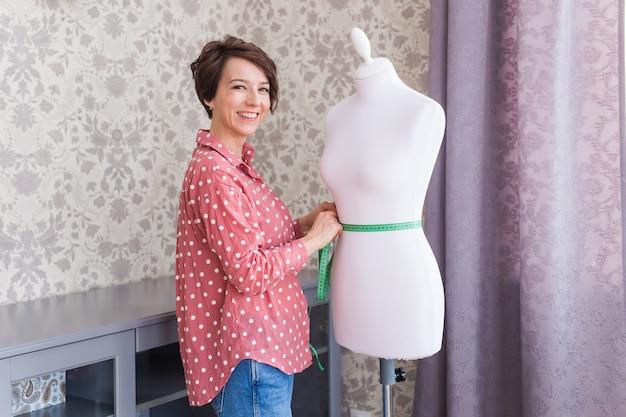 Couturière tenant un mètre ruban sur mannequin en studio de design créatif