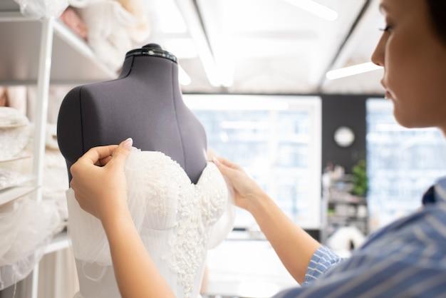 Couturière travaillant sur la robe de mariée