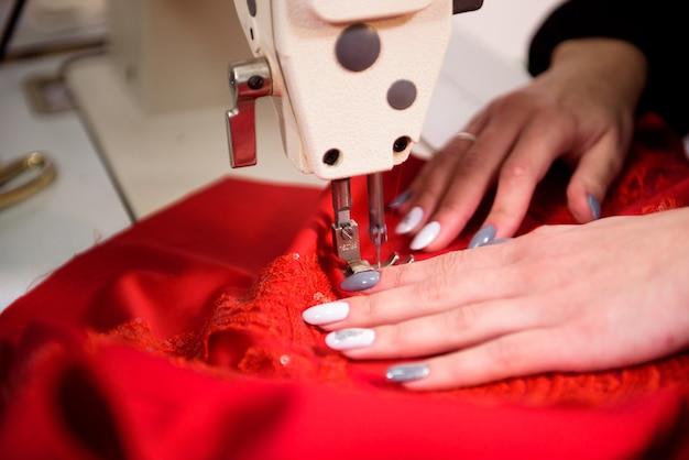 Couturière travaille à coudre des vêtements dans une machine à coudre, gros plan des mains.