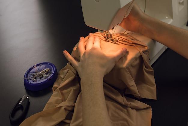 Couturière travaille sur une machine à coudre. la femme coud et tient un tissu rose, close up