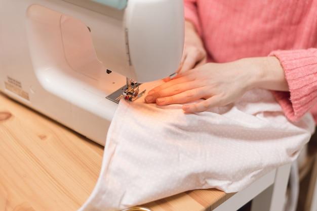 Couturière travaille sur une machine à coudre. la femme coud et tient un tissu rose