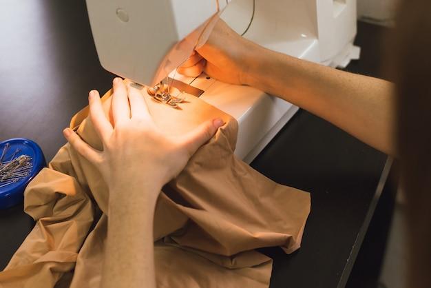 Couturière travaille sur une machine à coudre. la fille coud et tient un drap rose