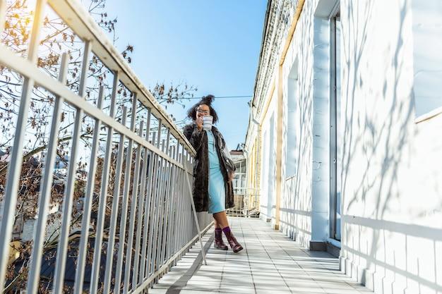 Couvert de manteau. heureux jeune femme se détendre dans les lumières du soleil avec une tasse à la main