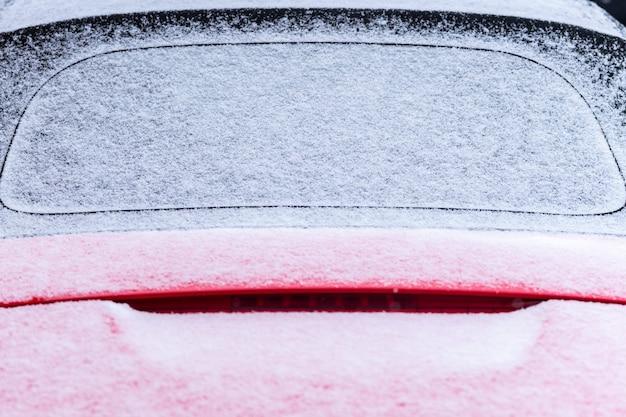 Couvert de neige sur le capot de la voiture
