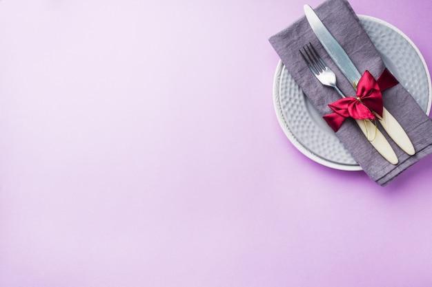 Couverts, assiettes couteau et fourchette avec serviette sur fond rose. concept de table de vacances