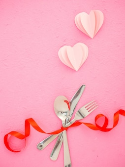 Couverts et coeurs sur la table rose