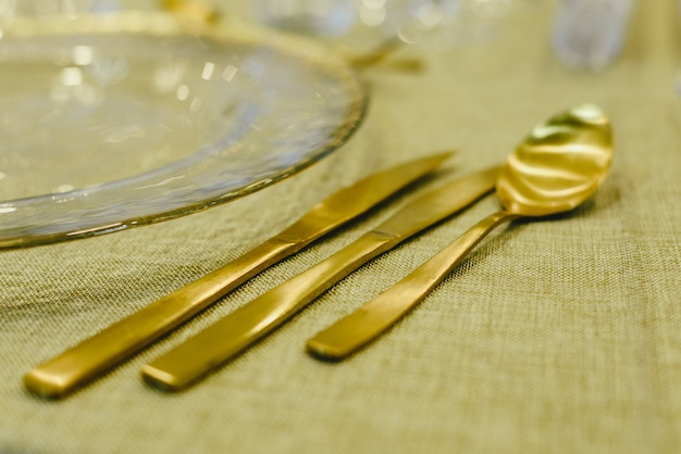 Couverts de luxe en or pour des occasions spéciales telles que noël sur une table avec une nappe rustique.