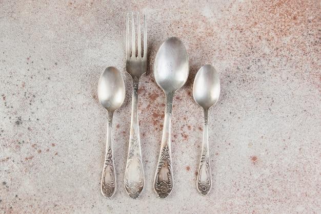 Couverts en métal antique sur table en béton.