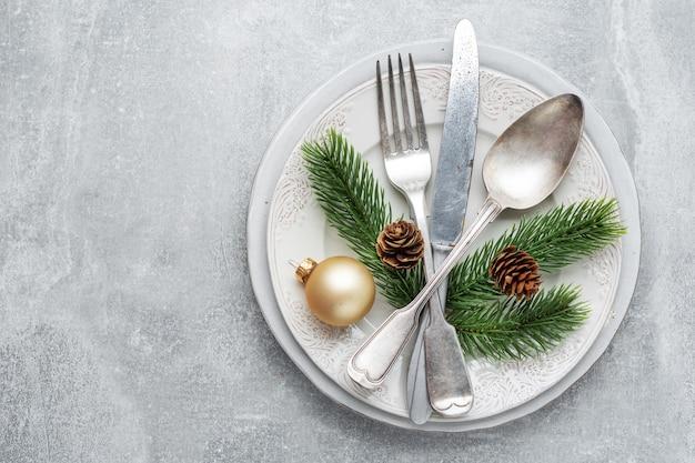 Couverts de noël sur assiette avec déco de noël sur table.