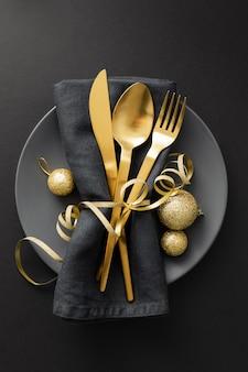 Couverts en or servis sur une assiette pour le dîner de noël