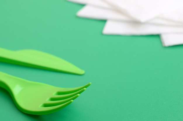 Couverts en plastique jetables verts. une fourchette et un couteau en plastique reposent sur une surface de fond verte à côté de serviettes