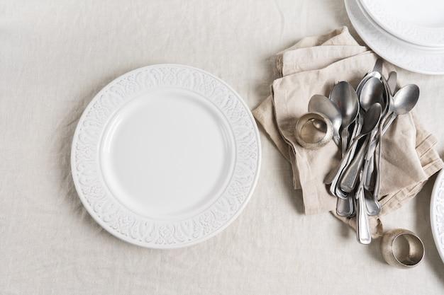 Couverts, serviettes, ronds de serviettes et assiettes sur une nappe en lin avec de l'espace. préparation au décor de table de fête.
