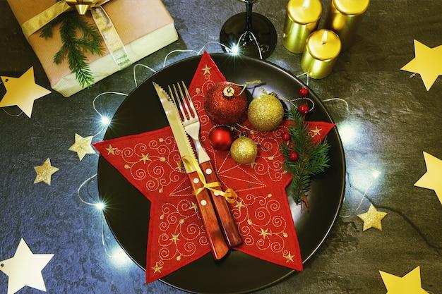 Couverts de table de noël. fond de vacances or rouge