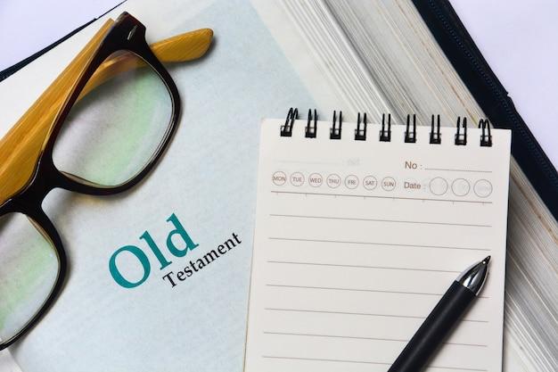 Couverture de l'ancien testament dans la sainte bible avec carnet, stylo et lunettes