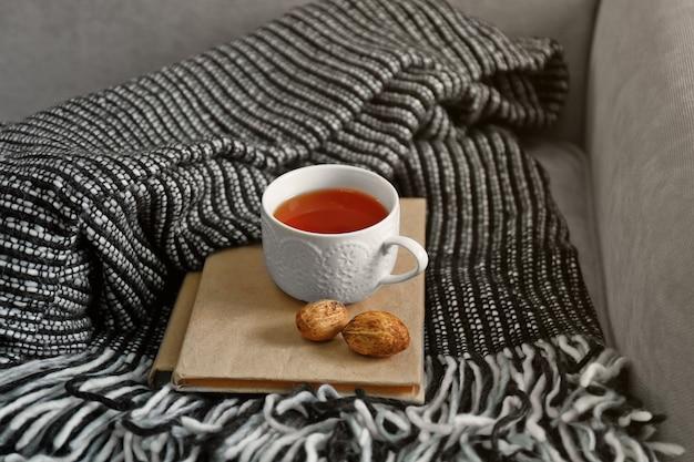 Une couverture douce, une tasse de thé, des noix et un livre sur le canapé. concept de paix et de confort
