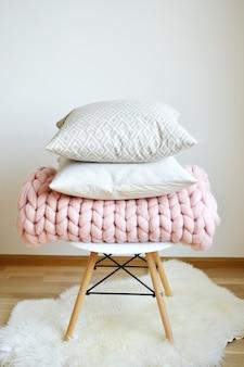 Couverture géante rose à carreaux en laine tricotée sur une chaise de tabouret en bois blanc de style scandinave
