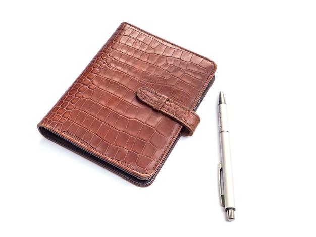 Couverture de livre journal en cuir et stylo sur fond blanc