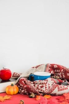 Couverture et mug près du livre et des fruits