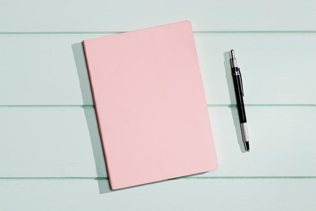Couverture rose d'un bloc-notes avec un stylo