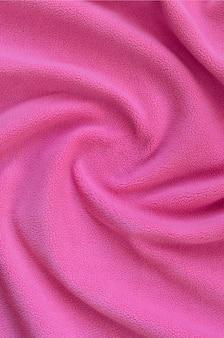 La couverture en tissu polaire rose velu. fond en peluche douce rose pâle avec beaucoup de reliefs