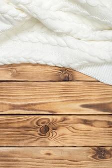 Couverture tricotée confortable sur des planches en bois