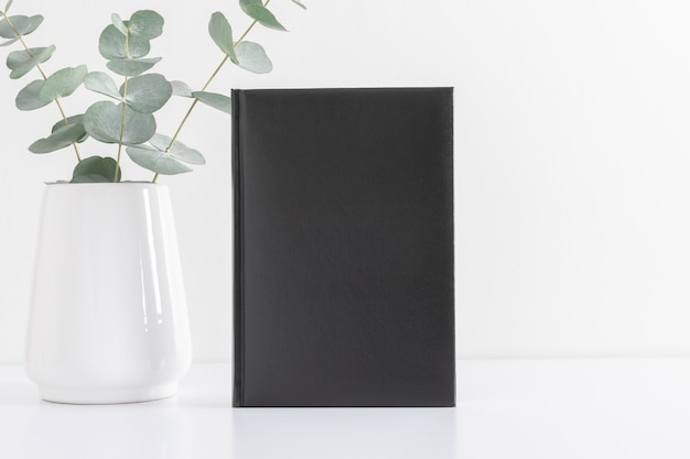 Couverture vierge d'un livre noir ou d'un journal avec une plante verte sur un tableau blanc