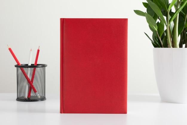 Couverture vierge d'un livre rouge ou d'un journal sur fond blanc avec des crayons et une plante sur un vase