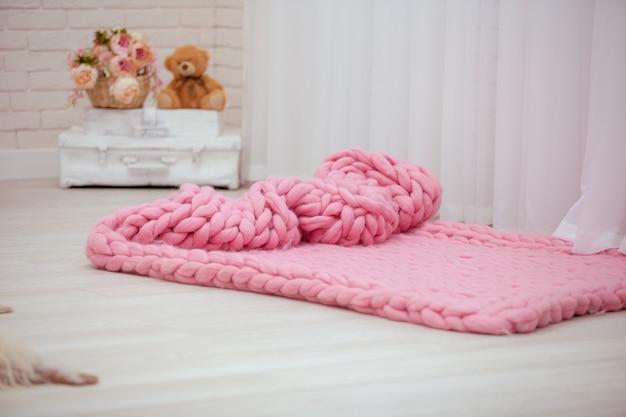 Des couvertures de créateur en mérinos rose étalées sur le sol.
