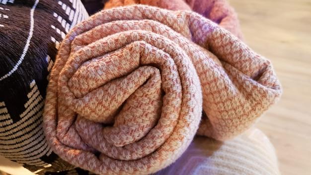 Des couvertures tricotées et chaudes sont pliées et déposées dans un panier en osier près de la cheminée. intérieur confortable dans la maison. détails d'un intérieur confortable moderne