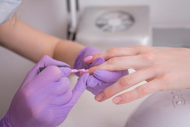 Couvrant les ongles avec du vernis à ongles rose.