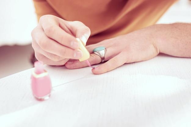 Couvrant ses ongles. jolie personne queer gingembre portant une grande bague en argent et peignant de petits ongles courts avec du vernis rose pour bébé