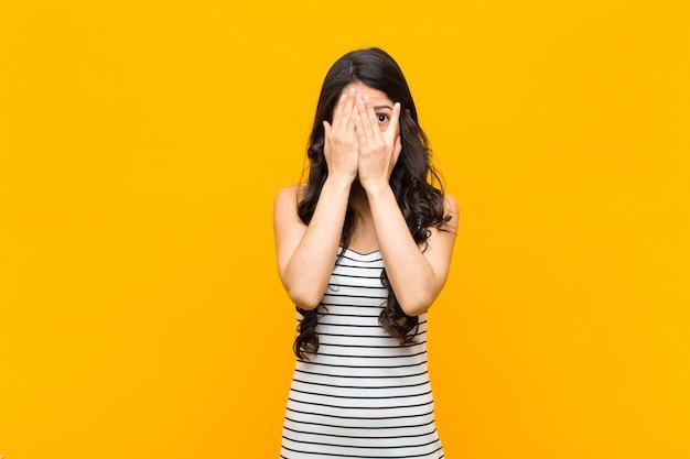 Couvrant le visage avec les mains, jetant un coup d'œil entre les doigts avec une expression surprise et regardant sur le côté