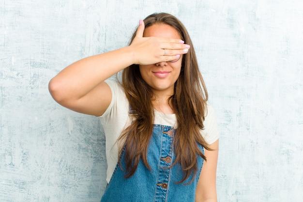 Couvrant les yeux d'une main, effrayé ou anxieux, se demandant ou attendant aveuglément une surprise