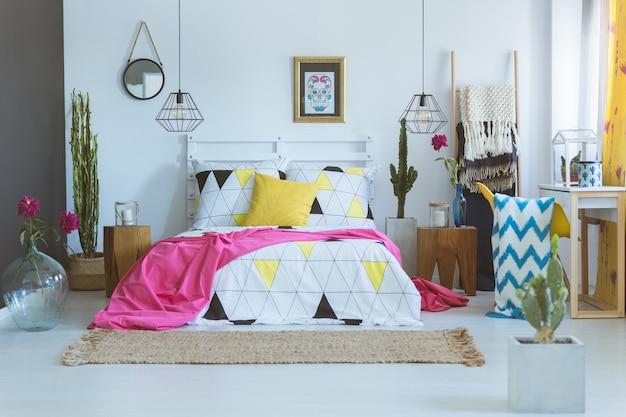 Couvre-lit à motif géométrique sur lit king-size dans une chambre unique. concept de chambre mexicaine