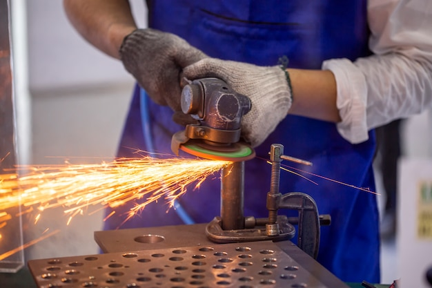 Couvreur à l'aide d'une meuleuse d'angle pour couper un métal.