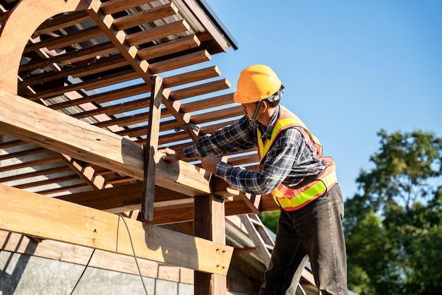 Couvreur, un charpentier travaillant sur la structure du toit sur le chantier de construction