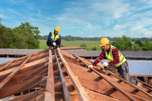 Couvreur, constructeur de couvreurs de deux ouvriers travaillant sur la structure du toit sur le chantier de construction, concept de construction de travail d'équipe.