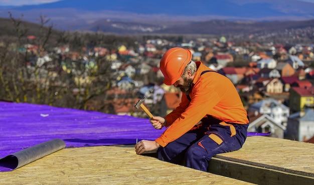 Couvreur construisant un nouveau toit. surface de toiture du constructeur. toit de réparation de maître professionnel. pose de toit plat. bâtiment de construction. matériaux en feuille imperméables. travaux en haute altitude. isolation thermique.